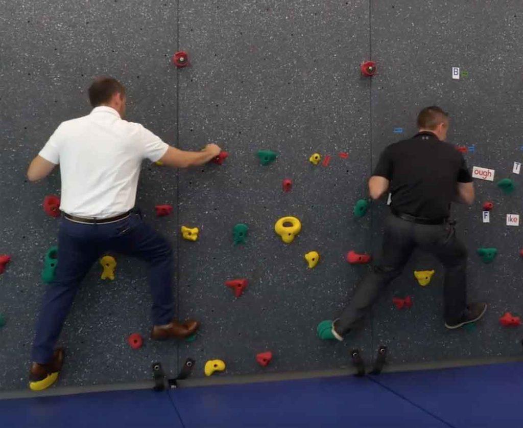Roswell Realtors Matt and Jeremey Ashman on the climbing wall at Building Kidz School
